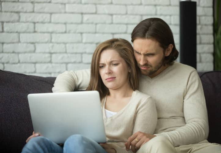 Unhappy couple looking at email spam on a laptop