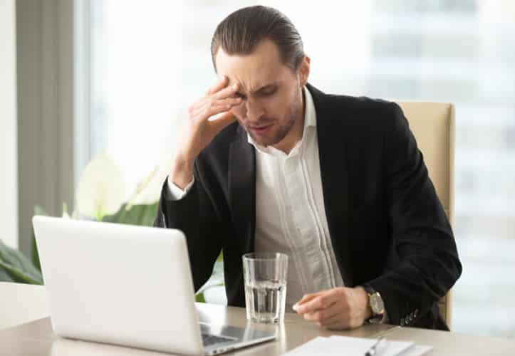 Unhappy office manager using a laptop in a clean office