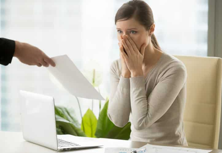Female employee looking shocked as she is handed a piece of paper.