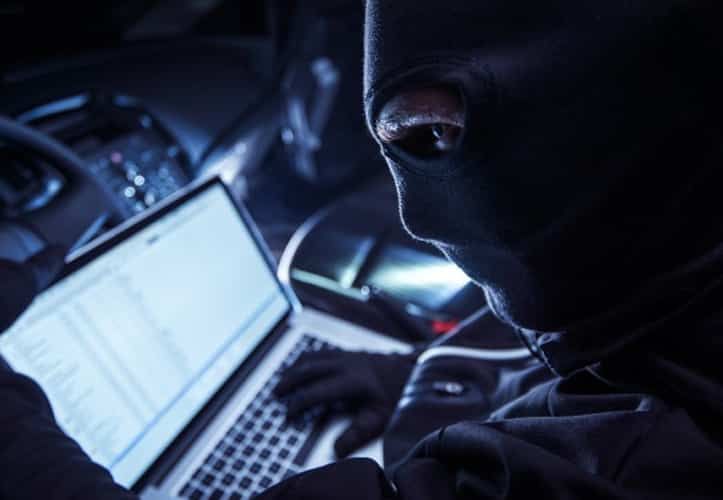 Suspicious man trying to install ransomeware on an organisation's server in a dark room
