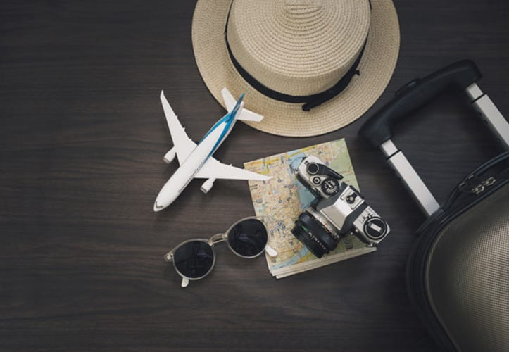 Travel accessories laid out on a wooden background