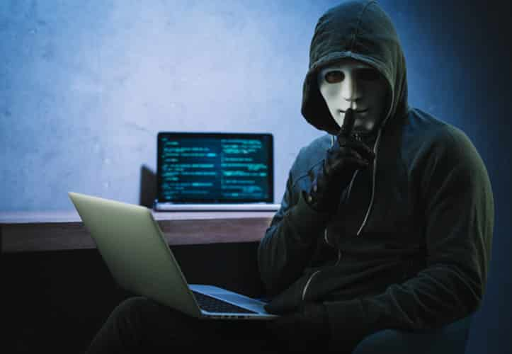 Man in hoodie and a mask looking at camera while he hacks into a business computing system