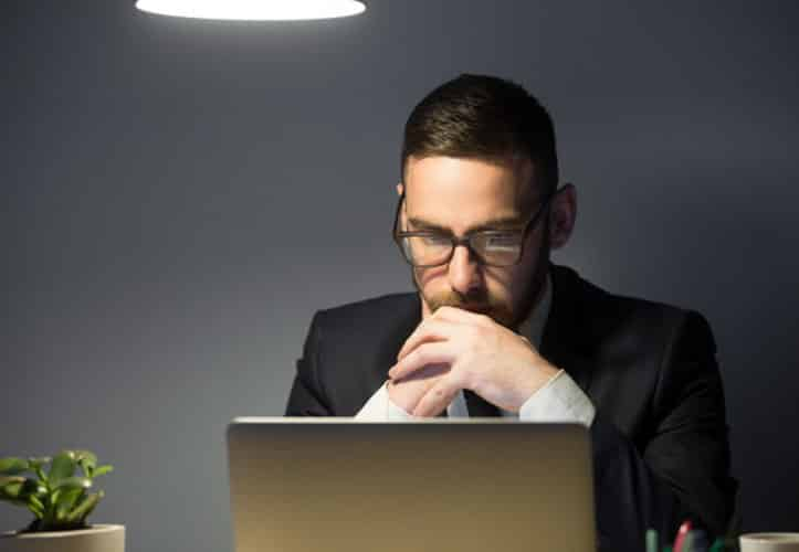 Businessman intently reading something on his laptop