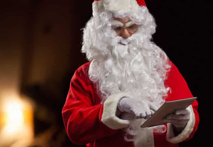 Santa Clause using an iPad in front of a fire place at Christmas