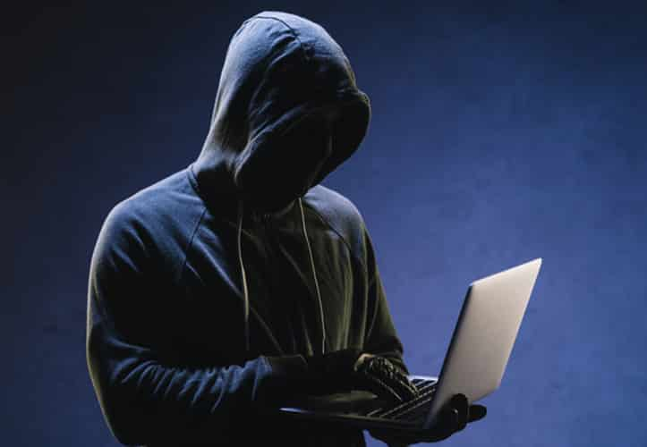 Person in a hoodie digitally attacking an organisation with ransomeware