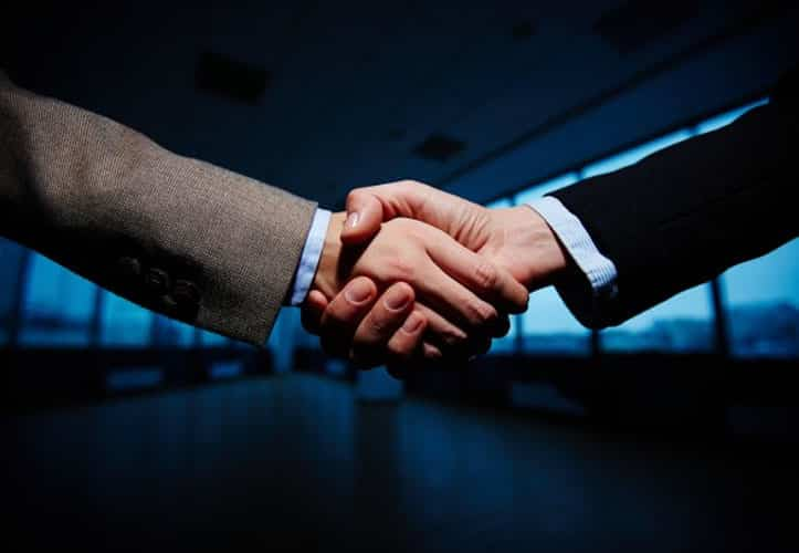 Two white-collar professional shaking hands in agreement