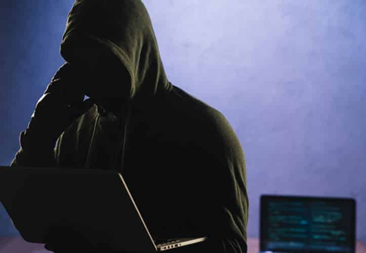 Silhouette of hacker in a dingy setting