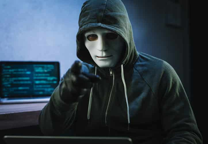 Man in hoodie and a mask pointing at camera while he hacks into a office IT system