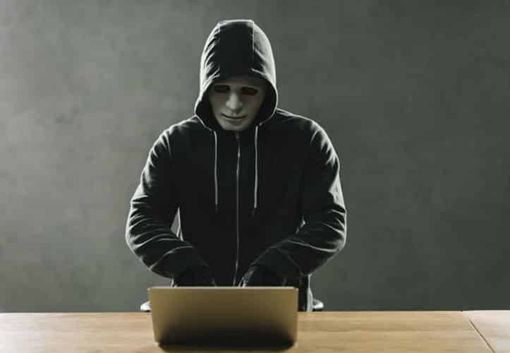 Persona in hoodie and a mask devising phishing scams for unsuspecting businesses.